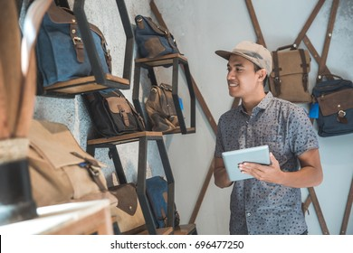 shop owner using tablet pc at his bag store