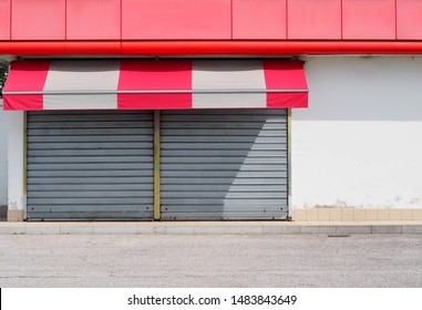 Shop retail with metal shutters closed and a red white awning. Sidewalk and asphalt road in front. Urban background for copy space