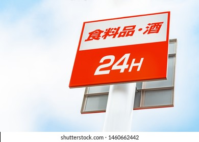 """Shop sign concept : Supermarket sign Open 24 Hours Service sign with blue sky background.Translation:  """"食料品"""" is """"Food""""  """"酒"""" is """"Alcohol"""" in Japanese."""