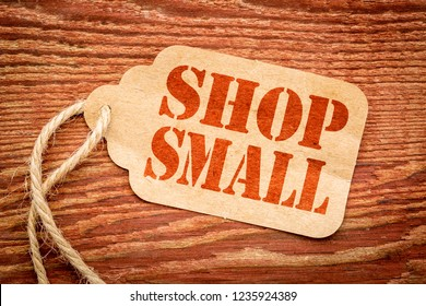 Shop Small - Small Business Saturday concept - a paper price tag with a twine against burlap canvas