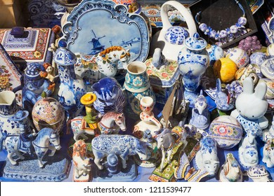 Shop window in Amsterdam with various second hand pottery, such as Delft Blue and Makkum.