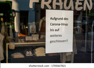 """Shop window of a shop with a sign """"Closed because of the Corona virus"""", in German, with displays and the reflection of the surroundings in blur at the time of Corona Covid-19 pandemic in March 2020"""