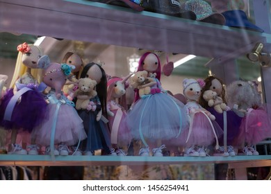 shop window, in which on the shelf are bright colorful various cute dolls in beautiful lush skirts and dresses