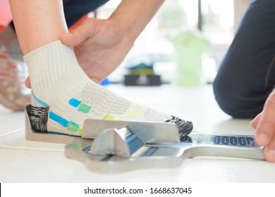 a shop worker measuring foot size