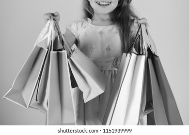 Shopaholic and childhood concept. Lady shopper in dress with wavy hair. Girl holds shopping bags on pink background, close up. Schoolgirl with red, pink and yellow packets does shopping. Shopaholic