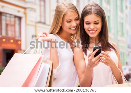 Shopaholic friends. Two attractive young women holding shopping bags and looking at mobile phone together while standing outdoors