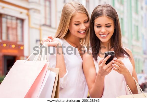 買い物中毒の友達。2人の魅力的な若い女性が、外で立ちながら買い物袋を持ち、携帯電話を見つめる