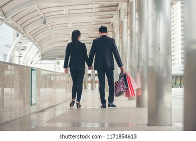 Shopaholic and lifestyle concept.Asian shopaholic woman shopping at department store,Happy Couple of love holding colorful shopping bag in fashion street,end of year sale.
