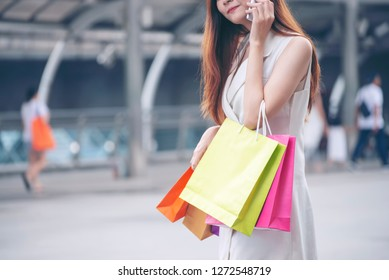 Shopaholic and lifestyle concept.Asian shopaholic woman shopping boutique clothes at department store,Happy Young shopper holding colorful shopping bag in fashion street,end of year sale.