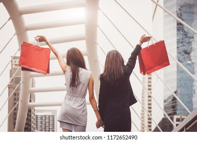 Shopaholic lifestyle friendship women holding shopping bag in shopping mall center. Black Friday and cyber Monday sale concept. Rich and luxury buyer having money for purchase wanted item or cosmetic.