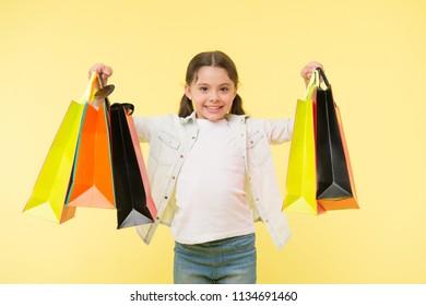 shopaholic. little shopaholic with many shopping bags. little girl shopaholic on black friday sale. beautiful shopaholic.