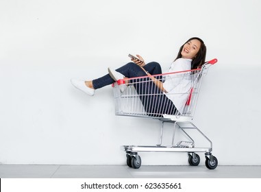 shopaholic pretty asian girl touch mobile phone in shopping cart as shopping online concept on white background