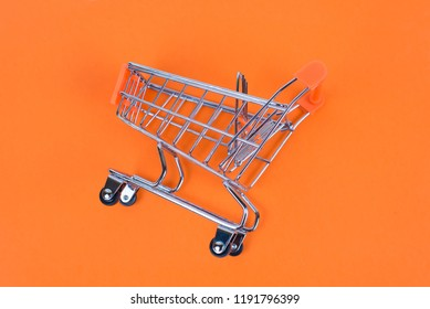 Shopaholic shopper ad concept. Close up top above overhead high angle close up view photo of one shine tiny toy colorful pushcart isolated on juicy saturated background copy space