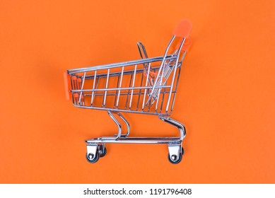 Shopaholic shopper ad concept. Close up top above overhead high angle close up view photo of one single shine tiny toy pushcart isolated on juicy saturated color background copy space