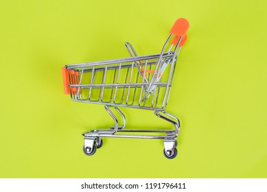 Shopaholic shopper ad concept. Close up top above overhead high angle close up view photo of one single shine tiny toy pushcart isolated on juicy saturated green color background copy space