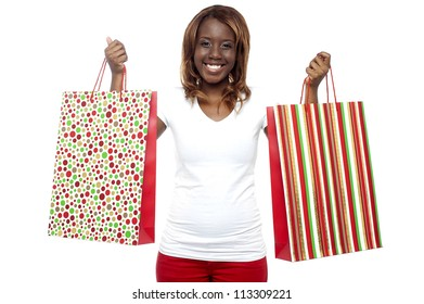 Shopaholic woman carrying shopping bags in both the hands isolated against white
