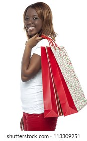 Shopaholic young girl carrying shopping bags over her shoulders