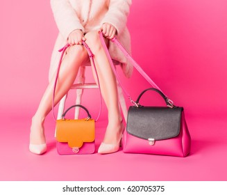 Shopaholic young woman in a coat in front of pink backgrund sitting on a chair and holding straps of a two woman's handbags standing nearby