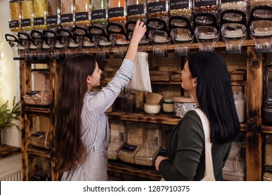 Shopkeeper assisting customer in packaging free shop. Zero waste shopping - woman buying healthy food in package free store.