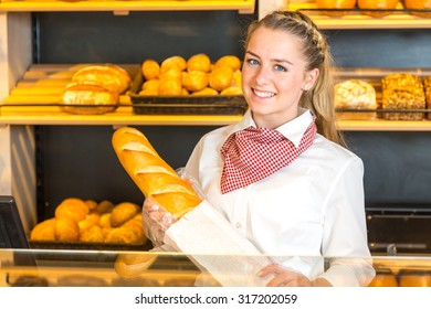 Shopkeeper in bakery putting loaf of bread into paper bag