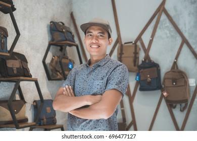 shopkeeper at his bag store smiling to camera