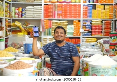Shopkeeper Showing Her Phone OR Mobile In Her Hand Portrait of A Shopkeeper Smiling Face Background Shop at `````Dhaka Bangladesh photo taken date 3-4-2021