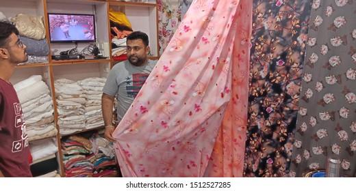 shopkeeper showing sari to the male customer in showroom at district Katni Madhya Pradesh in India shot captured on sep 2019