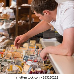 Shopkeeper working in a cheese glass case in a grocery store