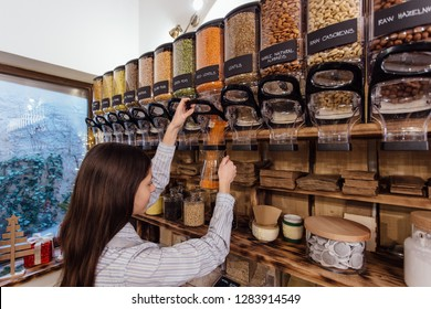 Shopkeeper working in zero waste shop. Shop assistant filling glass jar with red lentils in packaging free grocery store.