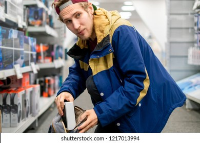 shoplifter in the electronic store supermarket stealing new gadget