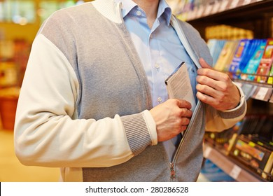 Shoplifter stealing bar of chocolate in a supermarket