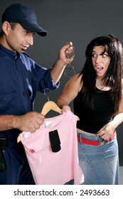 Shoplifting is a crime.  A security guard dangles handcuffs at a shoplifter.  Retailers lose $25 million a day to shoplifting.