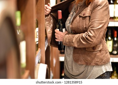 shoplifting - a woman steals a bottle of wine in a supermarket