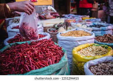 A shopper buying spicy Yunnan chills peppers in a Dali China street market.