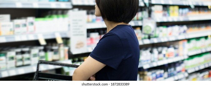 Shopper examining medical goods at pharmacy. Focused on back middle of shirt. Woman picking daily food supplements in store. Insurance, medical care concept.  Woman choosing vitamins and supplements.