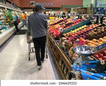 Shopper in fruit and vegetable aisle in local Publix grocery store Saint Augustine, Florida USA. March 13, 2018
