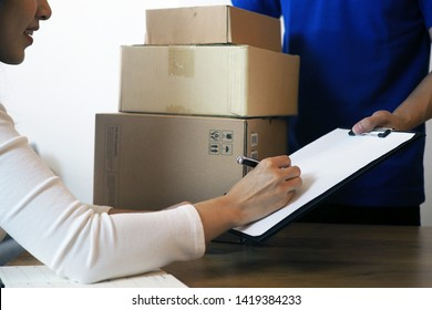 The shopper girl signs on the clipboard to receive the package box from the delivery man. Fast delivery service