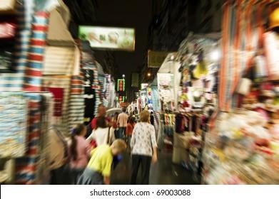Shopper at Hong Kong night market, purposely blurred.