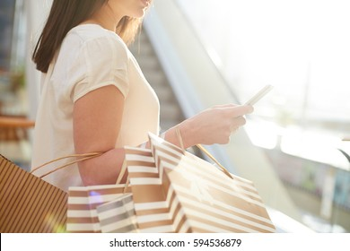 Shopper with paperbags messaging after shopping