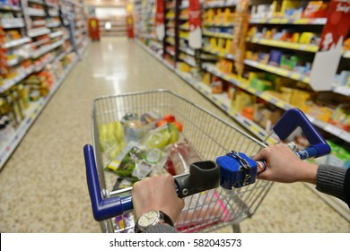 Shopper Pushes a Cart with Grocery Products in Supermarket Aisle - Image Has a Shallow Depth of Field