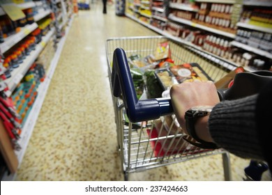 Shopper Pushes a Cart in Supermarket Aisle - Image Has a Shallow Depth of Field