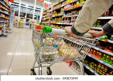 A Shopper Pushes a Trolley along a Supermarket Aisle - Image has a Shallow Depth of Field