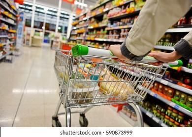 Ein Shopper schüttelt einen Trolley entlang eines Supermarkt-Aisle - Bild hat eine langsamere Außentiefe