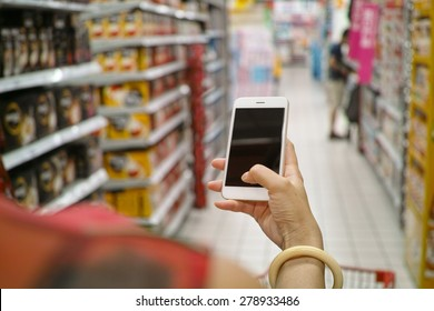 a shopper using mobile phone in supermarket