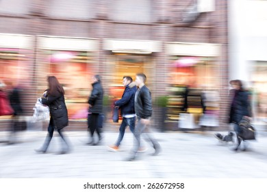 Shopper walking against shop window, zoom effect, motion blur