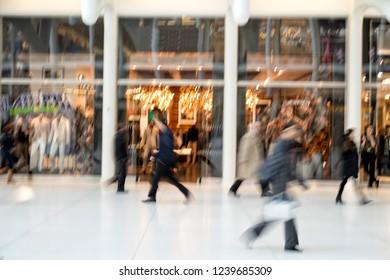 A shopper walking in front of shop window at dusk