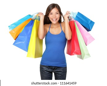 Shopper woman holding shopping bags. Young beautiful shopping woman on sale holding many colorful shopping bags isolated on white background. Pretty multiracial Asian Chinese / Caucasian female model.