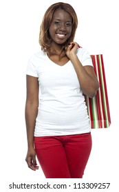 Shopper woman posing with shopping bag isolated over white background. Looking at you