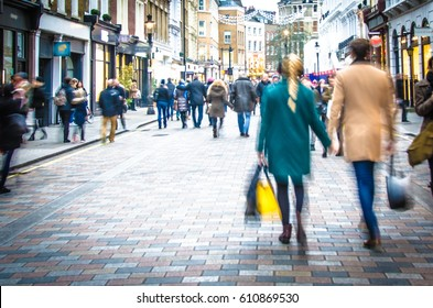 Shoppers holding hands in busy London high street