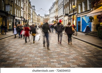 Shoppers walking down busy retail high street in London. Motion blurred